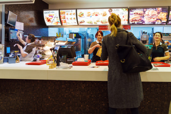 fast food workers serving a customer