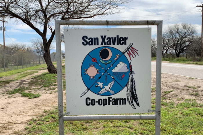 "The welcome sign outside the entrance reflects this agricultural history; it is a shield painted with a traditional planting stick and feathers representing a blessing. In the center is a sprouting seed, considered ""new life,"" and the four parts represent seasons containing the cycle of the sun, rain, moon, and wildlife. (Photo by Rudri Patel)"