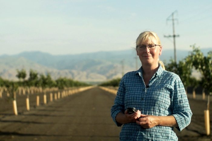 Antje Lauer standing in a newly planted orchard, where the bare soil could expose people to valley fever microbes