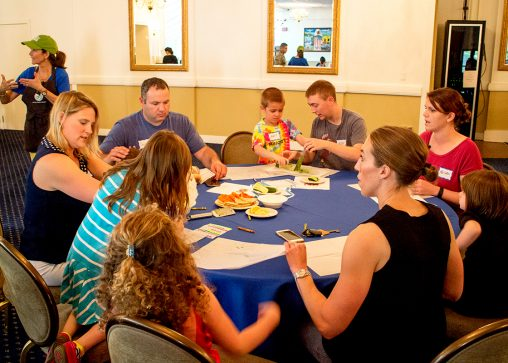 A community dinner at Hanscom Air Force Base produced in collaboration with Blue Star Families, a military family support organization. The families worked together to make tzatziki for a shared appetizer course. (Photo courtesy of The Family Dinner Project)