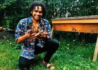 William Padilla-Brown holding reishi mushrooms near a beehive.