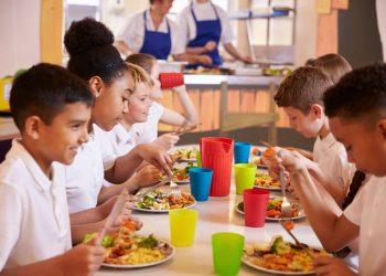 students dining in a cafeterial with their school lunches