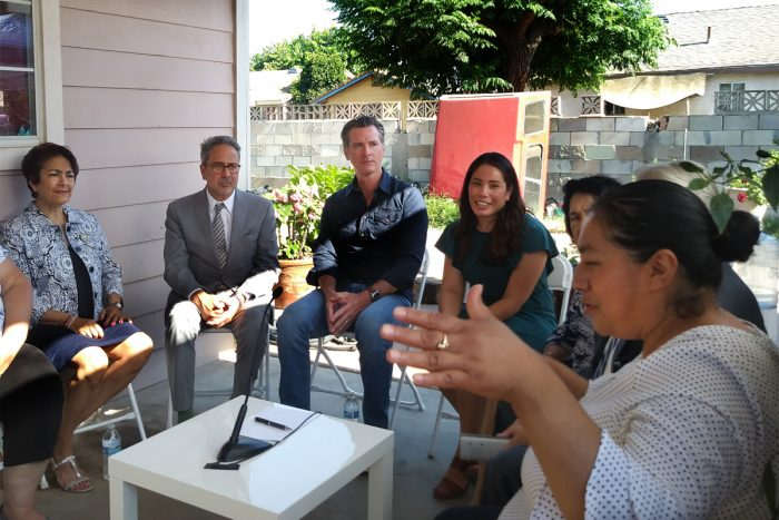 Governor Gavin Newsom (center) signs SB 200 at a home in the rural town of Tombstone in Fresno County with community residents, organizations, and State Senator Anna Caballero (left). (Photo courtesy of the Central California Environmental Justice Network).