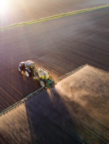 tractor spraying nitrogen fertilzer on a farm field
