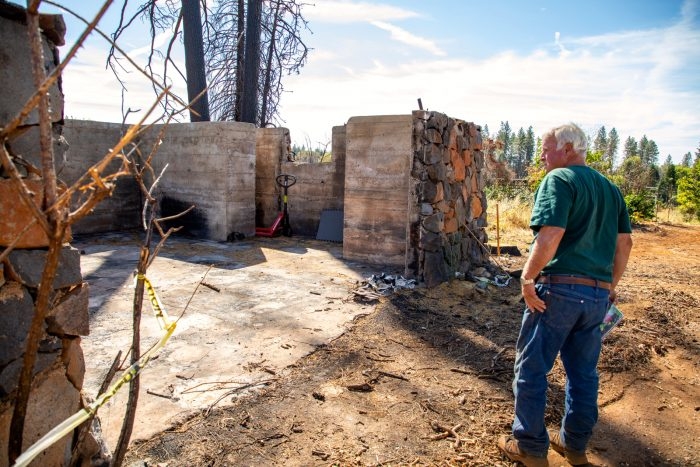 Jim checks on the stone walls remaining from a garage his grandfather built. The Camp Fire destroyed 11 buildings on the 18-acre property, but the fruit trees survived.