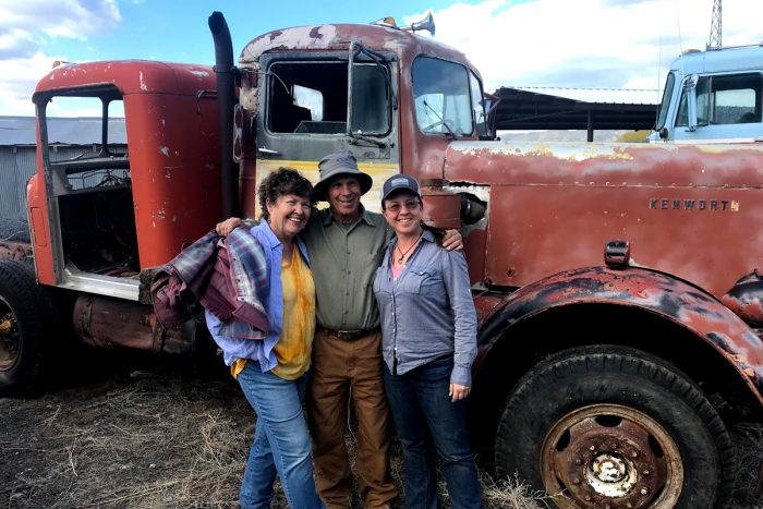 Becky Longberg and her parents standing by a farm truck.