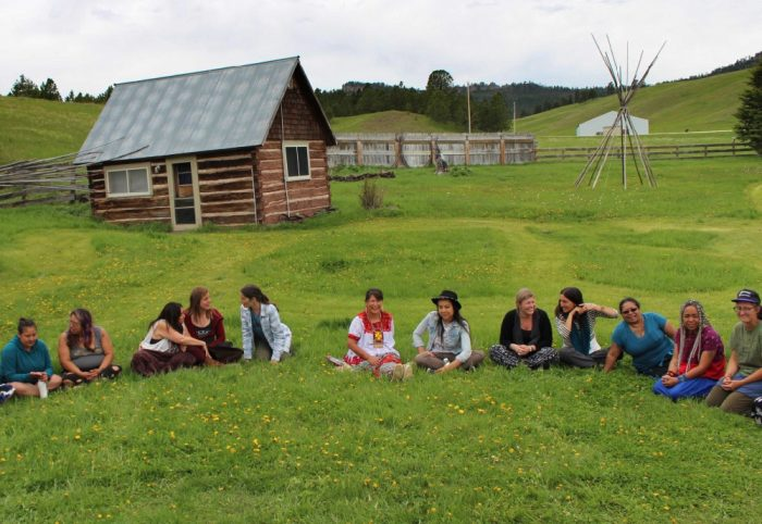 Water protectors of all persuasions gathered in talking circles at Borderland Ranch in Pe'Sla, the heart of the sacred Black Hills, during the first Sovereign Sisters Gathering. At the center are Cheryl Angel in red and white and on her left, Lyla June.