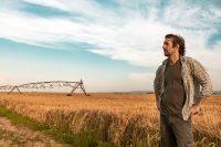 worried farmer standing in his farm field