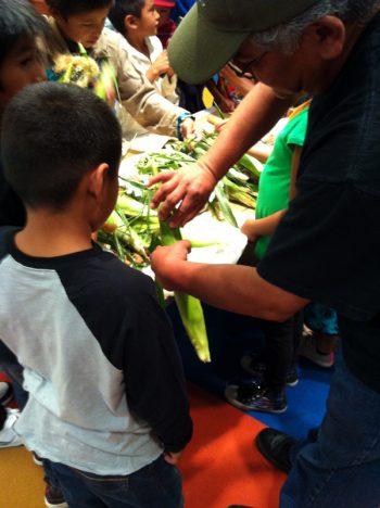 Natwani for Youth teaching Hopi children about preparing corn.