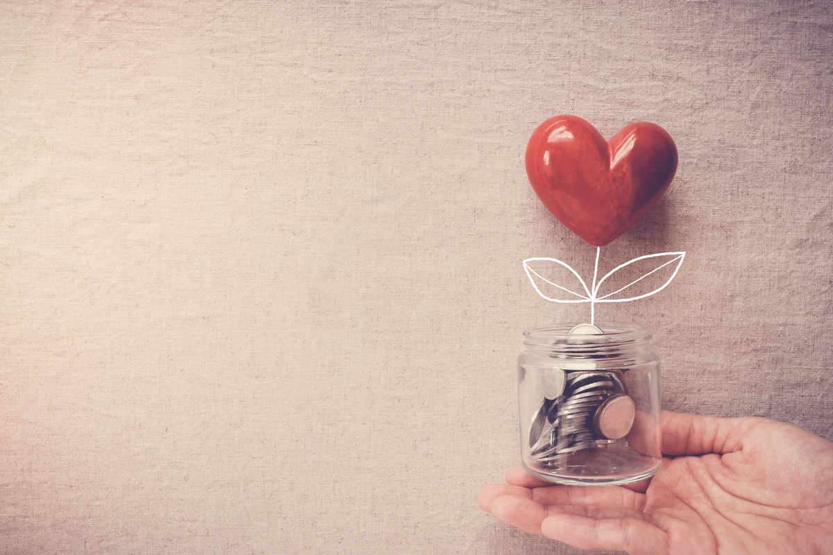 hand holding a coin jar and a heart balloon for givingtuesday or givingnewsday