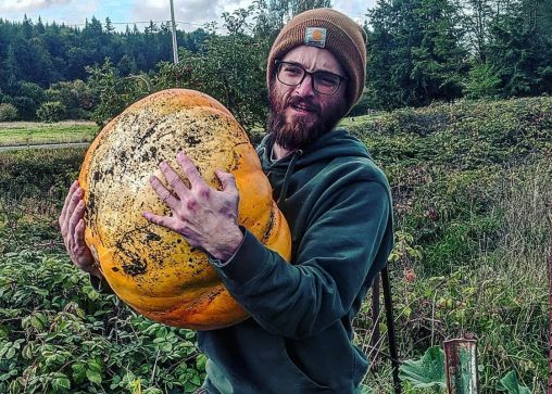 Young farmer struggling under the weight of a large squash.