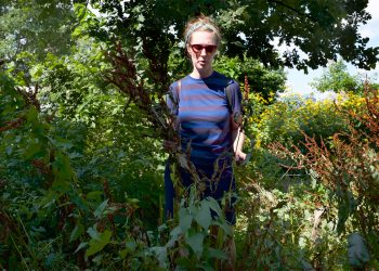 Candace Thompson standing in nature with edible plants