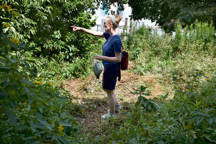 Candace Thompson pointing out some edible plants in a park.