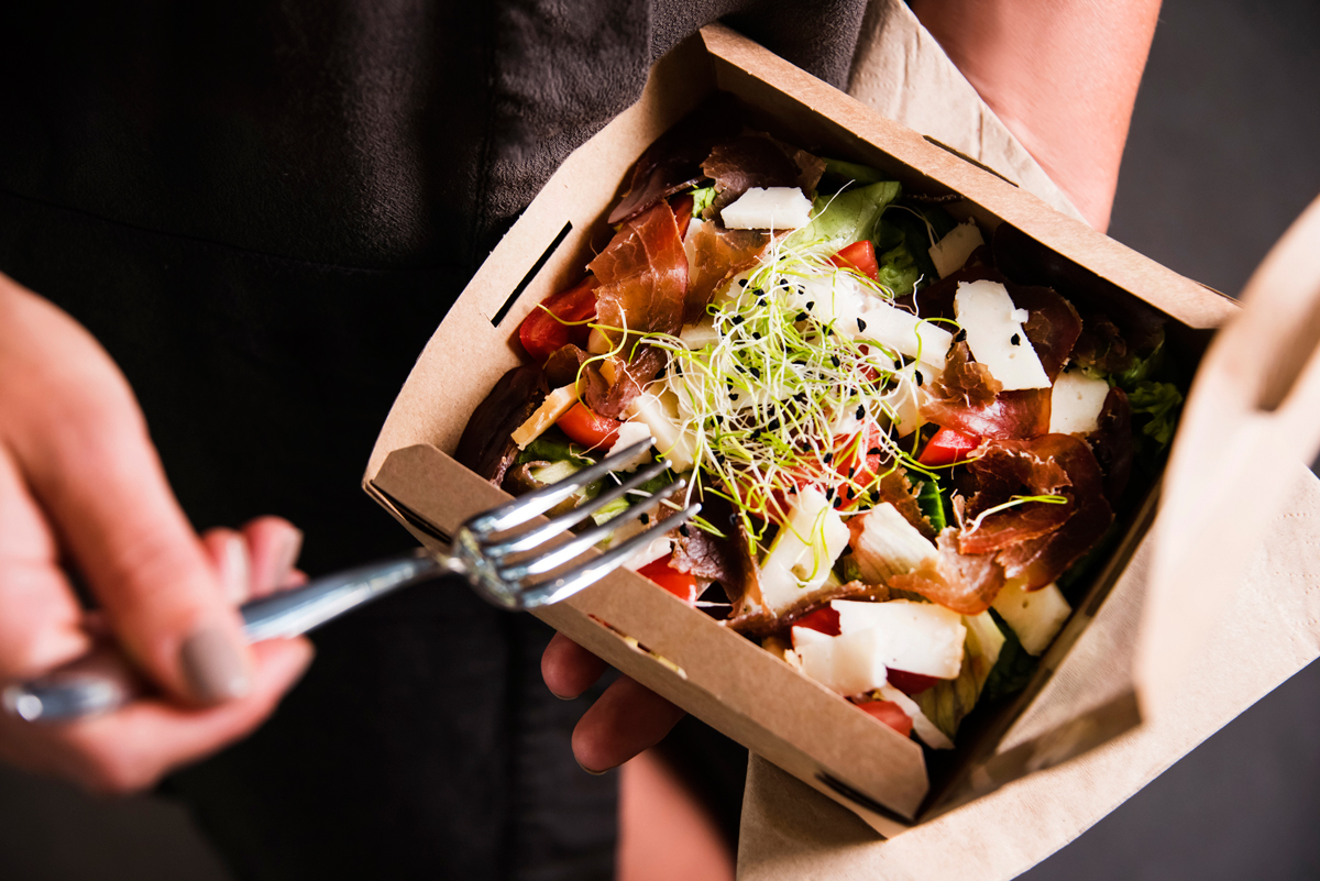 woman holding a compostable salad food take-out container