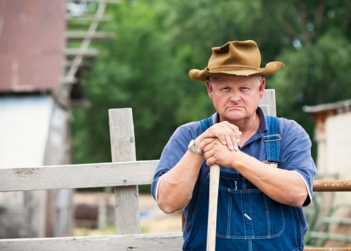 depressed farmer standing outside his barn, looking sad and hoping for smarter policy solutions