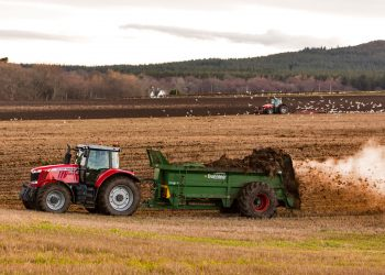 tractor spreading biosolids as fertilizer over farmland