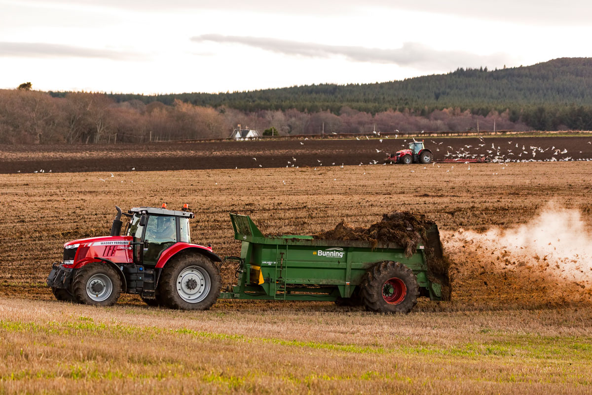 tractor spreading biosolids as fertilizer over farmland
