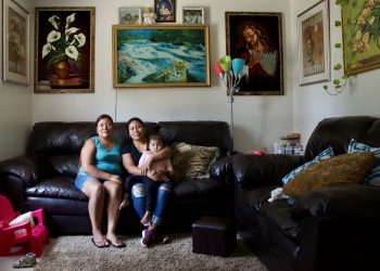 two women farmworkers in a living room.