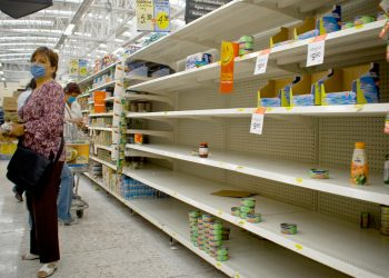 A woman wearing a mask stands in the aisle of a nearly empty grocery store amid a health crisis.