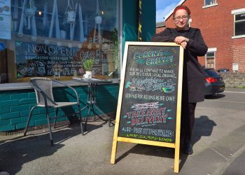 Restaurant owner stands outside a sign saying they're open during the coronavirus crisis. photo cc-licensed by Tim Dennell.