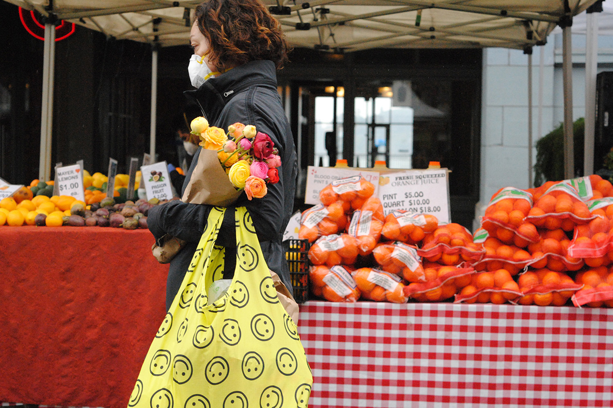 woman wearing a face mask shopping for produce and flowers