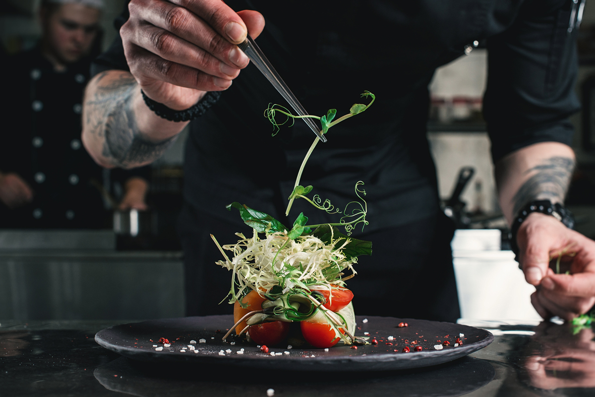 fine dining restaurant chef plating a healthy salad using local food from small farmers