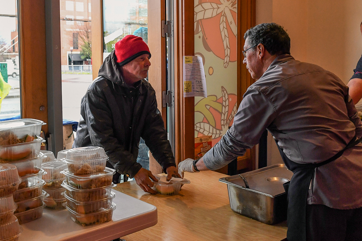 Handing out a take-out meal at Blanchet House. (Photo credit: Justin Katigbak)