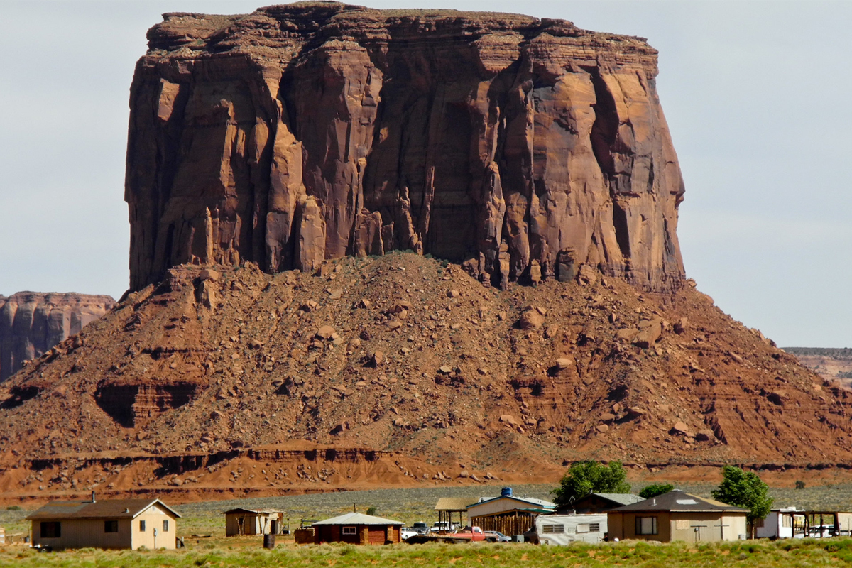 navajo nation homes in the community underneath a dramatic rock outcropping. Photo CC-licensed by Neil Moralee