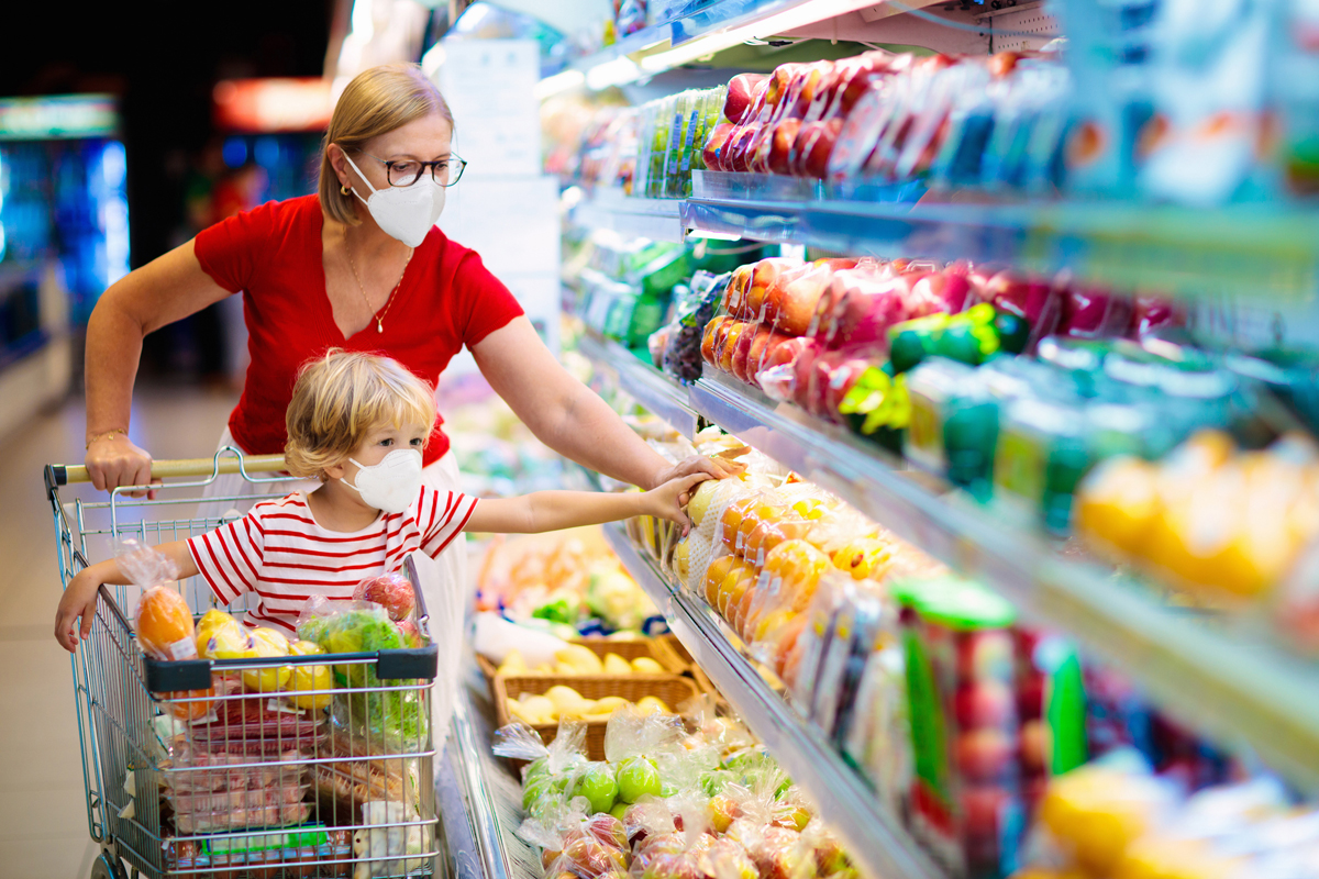 parent and child shopping for fresh produce while wearing masks and using pandemic ebt funds