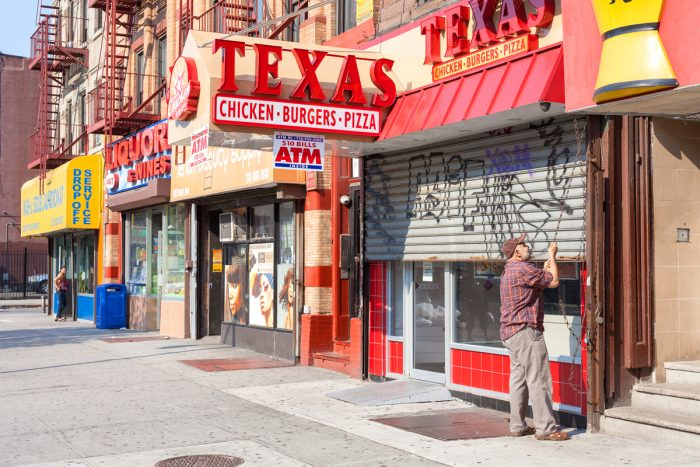 a street in harlem with fast food and liquor stores