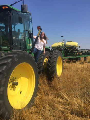 Raegan Cannon seeding a pasture with a no-till drill.