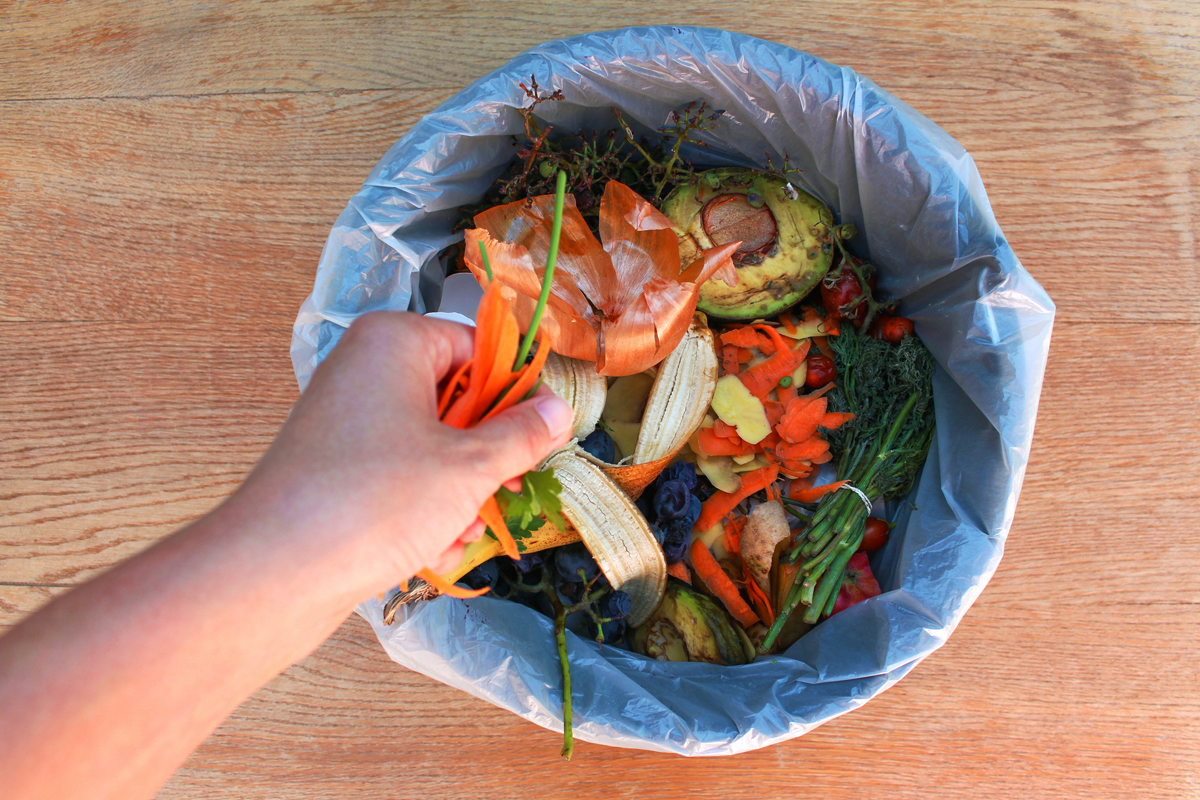 A hand putting food waste into a compost bin.