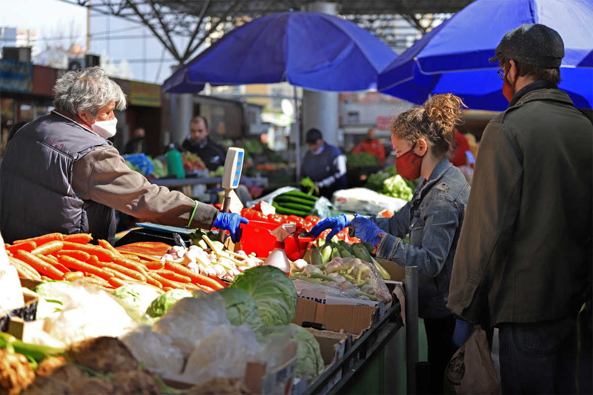 a woman shops at a farmers market using food assistance funds during the coronavirus pandemic