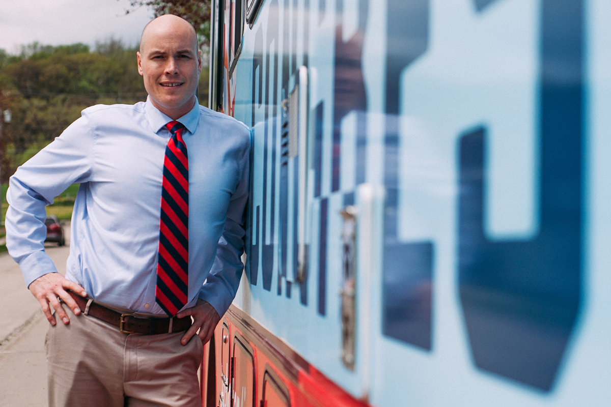 congressional candidate J.D. Scholten standing next to his campaign bus. Photo courtesy of Scholten for Congress.