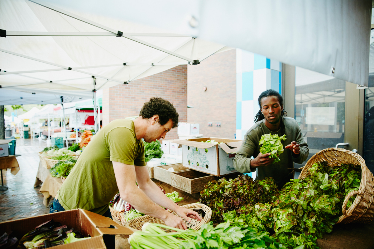 two men stocking a farmers market table to provide fresh local produce to shoppers