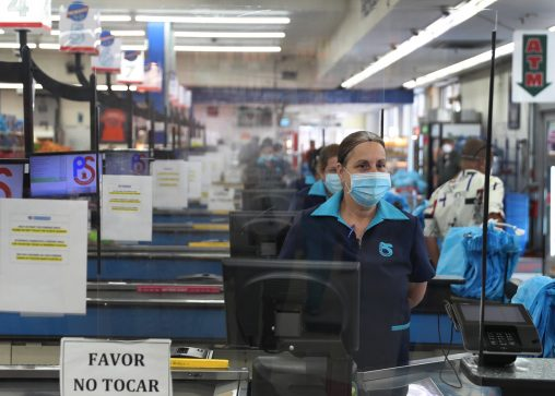 A grocery worker stands behind a partial protective plastic screen and wears a mask and gloves as she works as a cashier at the Presidente Supermarket in Miami, Florida. (Photo by Joe Raedle/Getty Images)