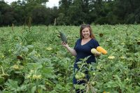 a woman harvesting squash in a chaos garden field