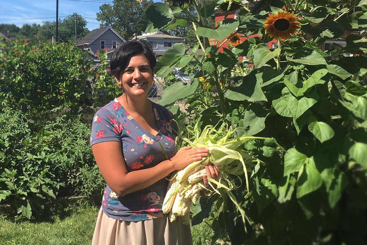 Shiloh Maples in the Sacred Roots garden holding Walpole Island flint corn. Some of the seed will be saved for the seed library and some will be used in food processing workshops. (Photo courtesy of Shiloh Maples)