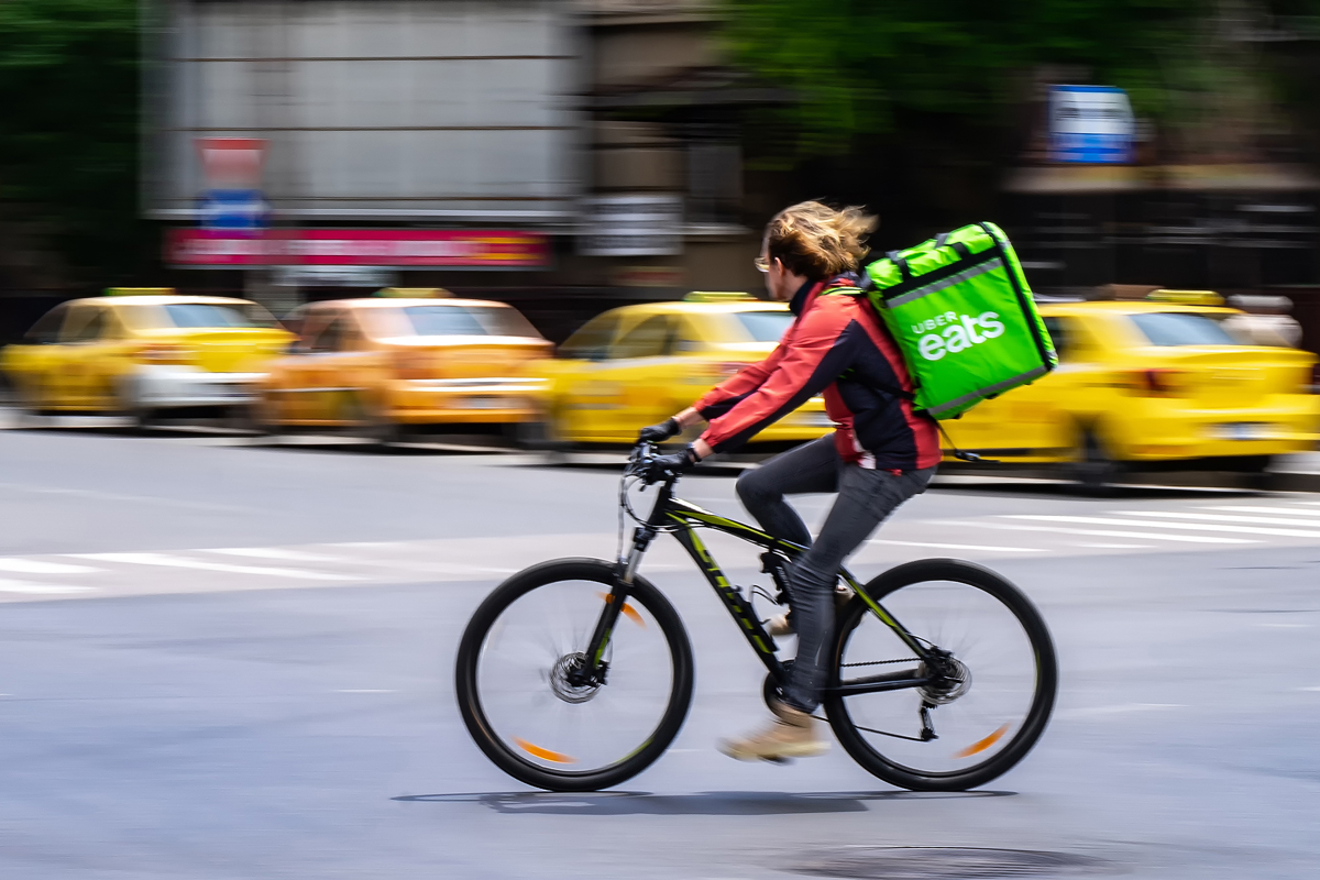 An Uber Eats food delivery courier on a bike in high speed. Restaurants are closed and only deliveries are allowed during the state of emergency due to coronavirus.