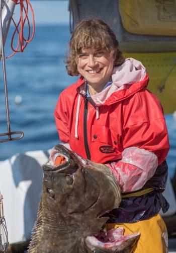 Linda Behnken holding a halibut. (Photo © Josh Roper Photography)