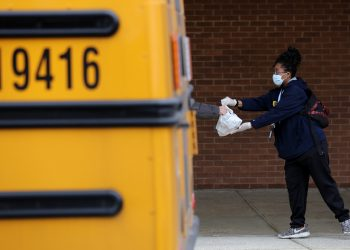 A Montgomery County (Maryland) Public Schools worker helps distribute bags of donated food as part of a program to feed children while schools are closed due to the coronavirus. (Photo by Chip Somodevilla/Getty Images)