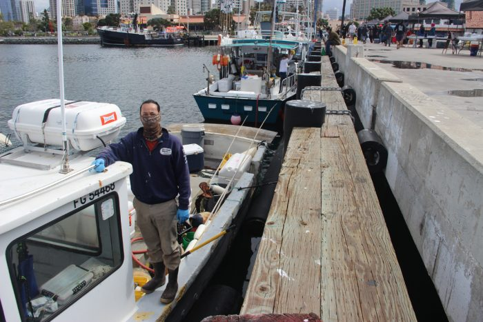 Dan Major stands on his boat at the Tuna Harbor Dockside Market, where he and his family sell rockfish and mackerel. (Photo by Mark Armao)