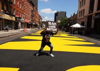"A man dances on a massive ""Black Lives Matter"" mural covering a city street in the Brooklyn borough of New York City. (Photo by Spencer Platt/Getty Images)"