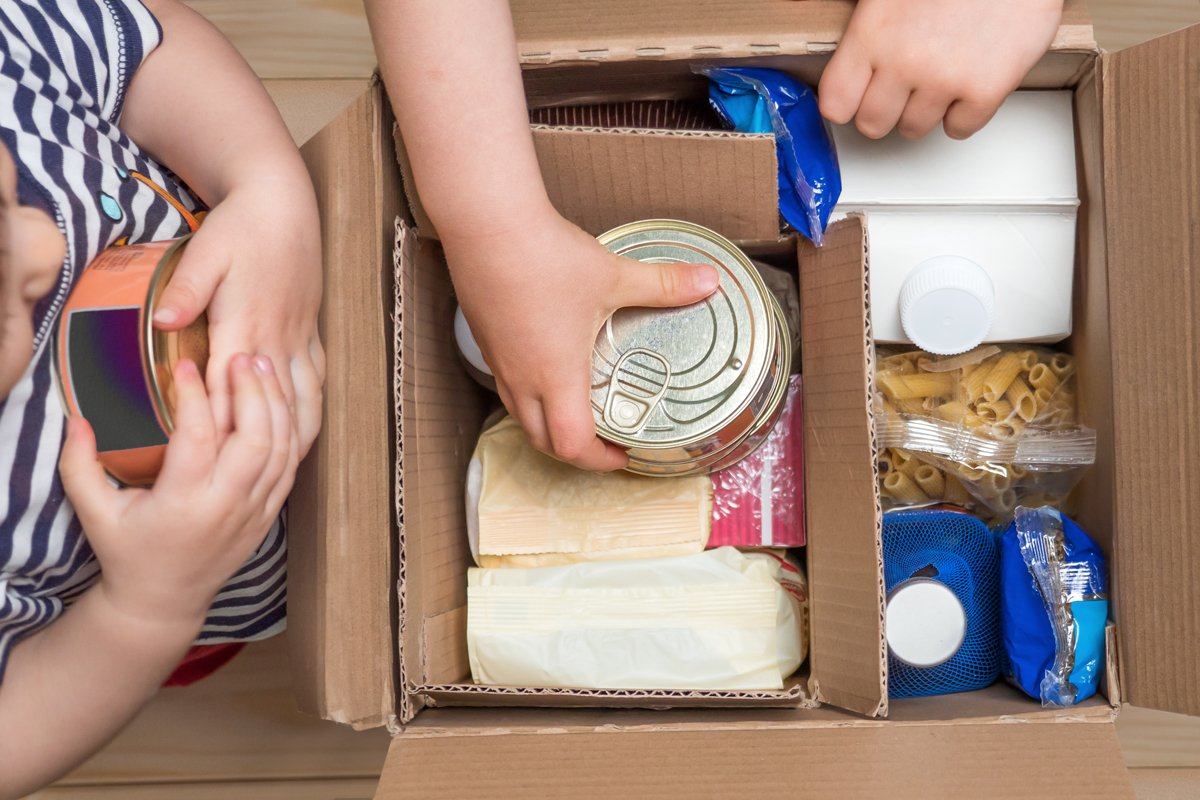 young people pull processed food out of a box of online snap orders