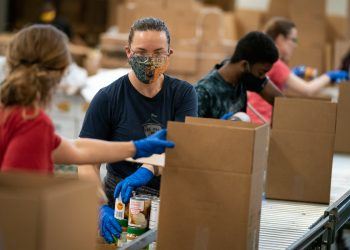 Volunteers pack up boxes of food to be distributed to those in need at the distribution center of the Capital Area Food Bank on April 9, 2020 in Washington, DC. (Photo by Drew Angerer/Getty Images)