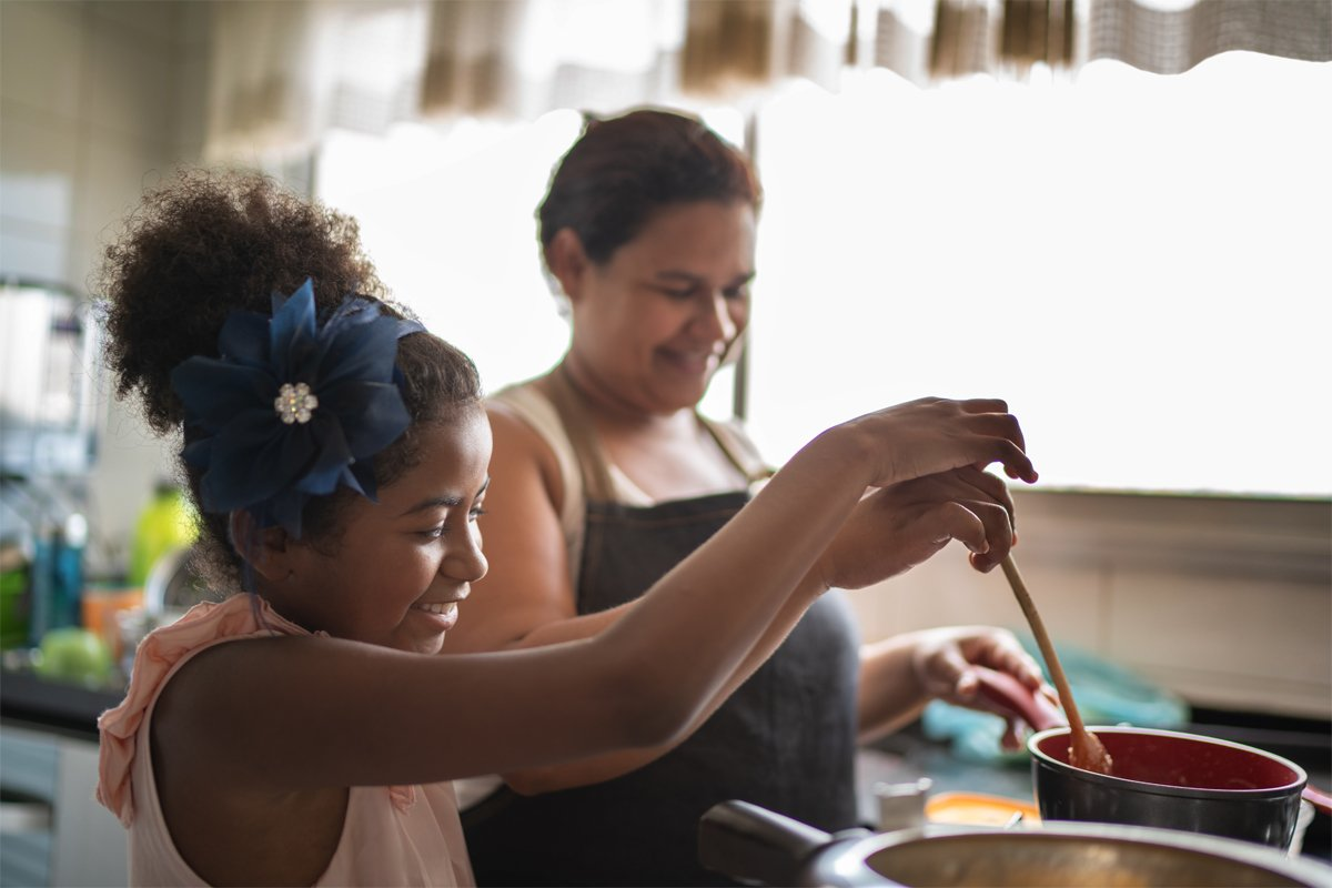 a woman of color and her child cook a healthy meal