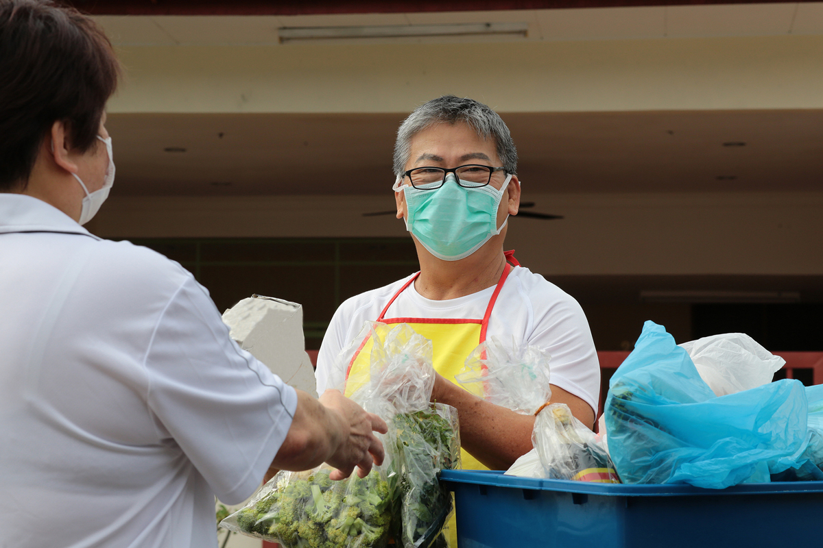 A man hands a bag of fresh produce to a shopper as part of a produce prescription program
