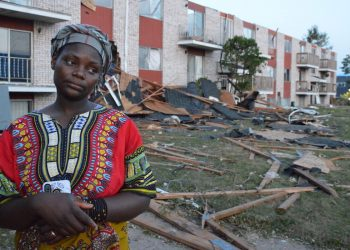 A woman stands outside the Cedar Terrace apartments after the derecho destroyed the building. Photo by Pat Rynard for Iowa Starting Line.