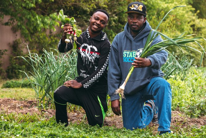 Two of New Roots' farmers show off some of their harvest. (Photo credit: IM Photography)