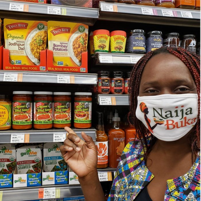 Lilian Ryland of Naija Buka shows her sauces on the shelf at a supermarket.